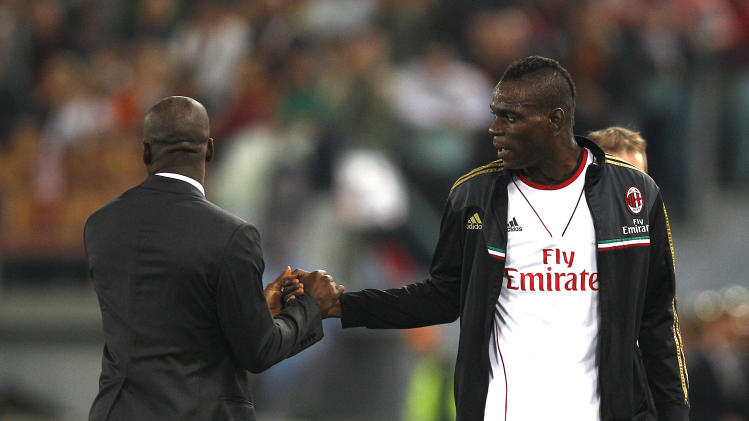 AC Milan's Mario Balotelli, left, salutes his coach Clarence Seedorf as he leaves the pitch during an Italian Serie A soccer match between Roma and AC Milan at Rome's Olympic stadium, Friday, April 25, 2014. (AP Photo/Alessandra Tarantino)