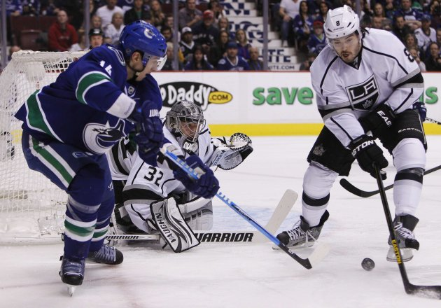 Vancouver Canucks' Burrows is stopped by Los Angeles Kings goaltender Quick while Kings' Doughty plays the puck during their NHL hockey game in Vancouver