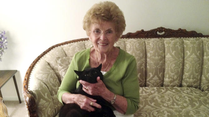 This Monday, July 16, 2012 photo provided by WMUR-TV shows Barbara Oliphant and her cat Wollie at her home in Bedford, N.H.  Animal rescue league officials said they don't know how the black cat walked about 6 miles in three days to find his way back home.  (AP Photo/WMUR-TV, Jean Macklin)