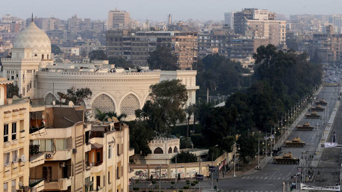 """View of the presidential palace guarded by military tanks in Cairo, Egypt, Sunday, Dec. 16, 2012. Key Egyptian rights groups called Sunday for a repeat of the first round of the constitutional referendum, alleging the vote was marred by widespread violations. Islamists who back the disputed charter claimed they were in the lead with a majority of """"yes"""" votes. (AP Photo/Hassan Ammar)"""