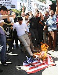 <p>Protesters burn a US flag during a protest against a US-produced film mocking Islam that they said was insulting to the Prophet Mohammad in front of the US Embassy in Ankara September 16, 2012.</p>