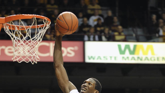 Minnesota's Trevor Mbakwe (32) goes in for a dunk over Iowa's Jarryd Cole, right, during the second half of an NCAA college basketball game Sunday, Jan. 16, 2011, in Minneapolis. Mbakwe finished with a team-high 16 points as Minnesota beat Iowa 69-59. (AP Photo/Tom Olmscheid)