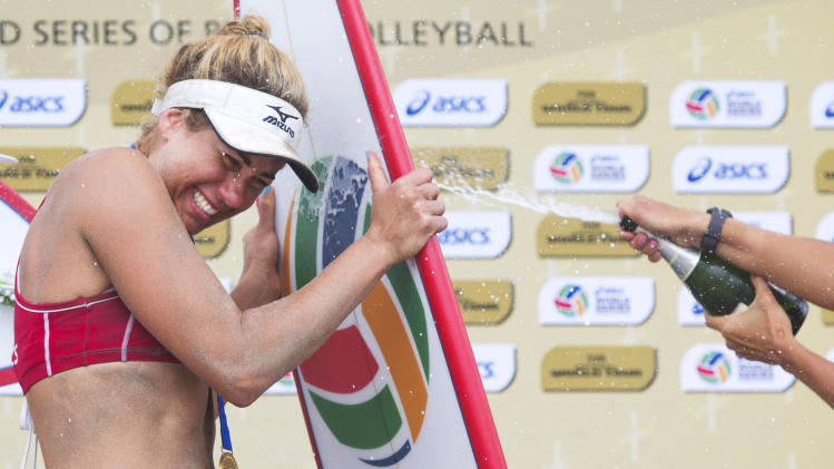 USA's April Ross is sprayed with champagne after placing first in the World Series of Beach Volleyball in Long Beach, Calif., Sunday, July 27, 2014. (AP Photo/The Orange County Register, Drew A. Kelly) MAGS OUT; LOS ANGELES TIMES OUT