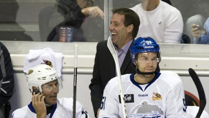Team Quebec coach Gaston Therrien, center, laughs as player Francois Beauchemin, left, of the Anaheim Ducks, talks on a cell phone during a television break during an exhibition hockey game against Team Montreal on Thursday, Oct. 11, 2012, in Quebec City. Player David Desharnais of the Montreal Canadiens sits on the board. Some of the locked out NHL players have organized a players' tour to raise funds for local charities. (AP Photo/The Canadian Press, Jacques Boissinot)