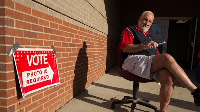 Bob Belew, a coach at Sylvan Park Elementary School in Nashville, Tenn., welcomes students and voters at a polling place at the school, on Tuesday, March 6, 2012. (AP Photo/Erik Schelzig)