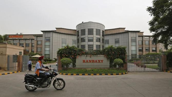 A man rides a motorcycle in front of the office of Ranbaxy Laboratories at Gurgaon