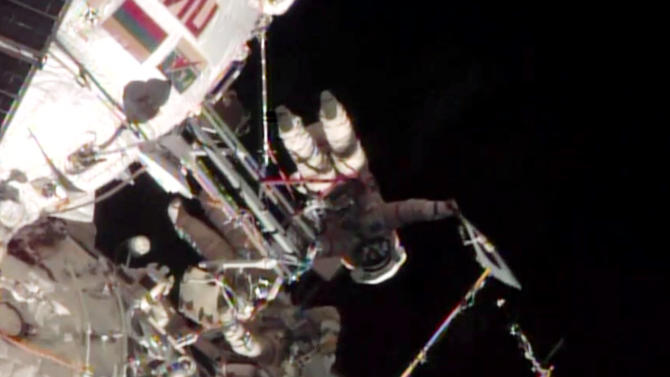 This screen image taken from NASA shows the Sochi Olympic torch being held during a spacewalk on Saturday, Nov. 9, 2013. Video streamed by the US space agency NASA showed Oleg Kotov and Sergei Ryazanskiy carrying the unlit Olympic torch, bobbing weightlessly at the end of a tether in a darkness dotted by stars. The two gingerly maneuvered to take photos of the torch against the background of the planet, the orb's edge glowing with sunrise. (AP Photo/NASA)