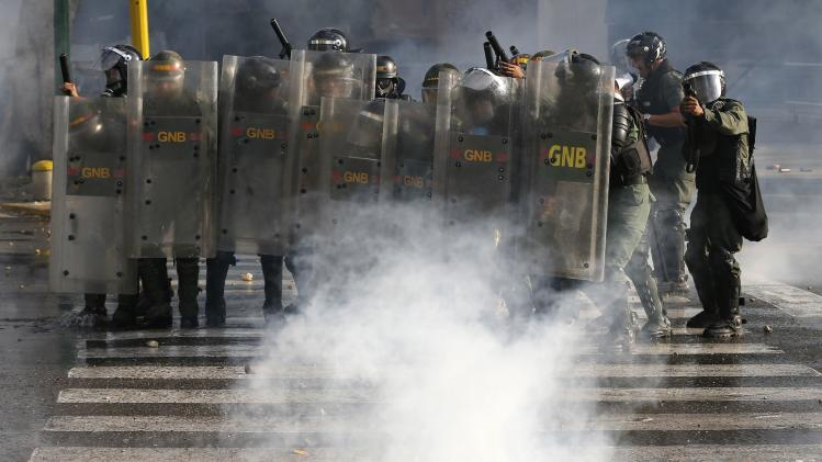 National Guards advance on anti-government protesters during clashes with police at Altamira square in Caracas