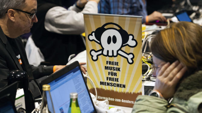"Members of the Pirates party sit next to a poster reading ""Free Music for Free People"" during their party convention in Neumuenster, northern Germany, Saturday, April 28, 2012. Pirates are capturing Germany's political system: The party started as a marginal club of computer nerds and hackers, but its appeal as an anti-establishment movement has lured many young voters to the ballot boxes, gaining it parliamentary seats in two consecutive state elections. (AP Photo/dapd, Clemens Bilan)"