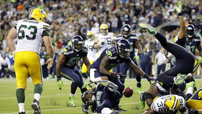 Seattle Seahawks players eye a fumble by Green Bay Packers'  Cedric Benson (32), lower right, that was recovered by Packers'  Jeff Saturday (63) in the second half of an NFL football game, Monday, Sept. 24, 2012, in Seattle. The Seahawks defeated the Packers 14-12. (AP Photo/Ted S. Warren)