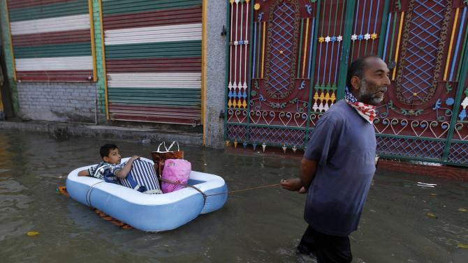 A Kashmir man pulls an inflatable raft carrying a boy through a flooded neighbourhood in Srinagar