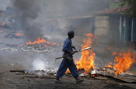 A policeman walks in front of a burning barricade during a protest against Burundi's President Pierre Nkurunziza and his bid for a third term in Bujumbura