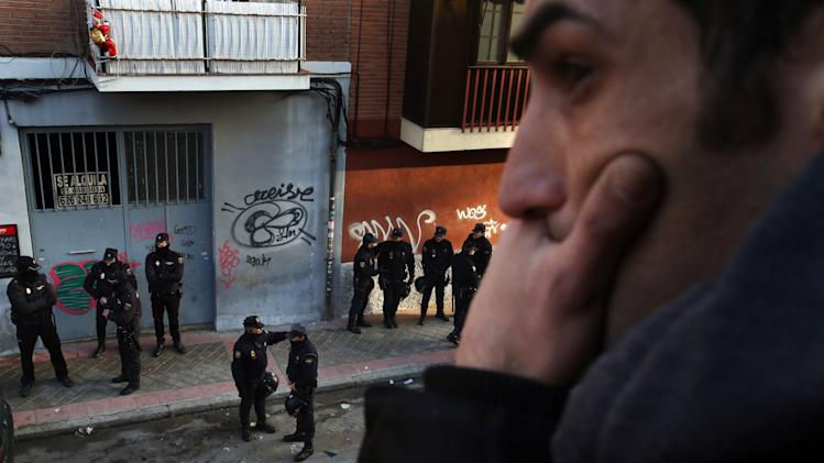An anti-eviction activist reacts as he watches Spanish police officers standing guard outside the home of John Jairo Nanez Betancur in Madrid