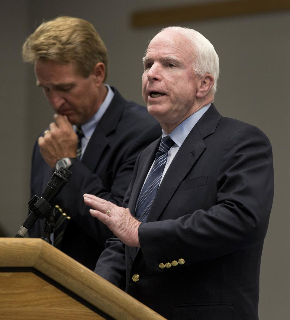 Sen. John McCain, right, R-Ariz., speaks during a news conference joined by fellow Sen. Jeff Flake, R-Ariz., Friday, July 5, 2013 in Prescott, Ariz. to discuss the fire that killed 19 Granite Mountain Hotshot firefighters last Sunday. (AP Photo/Julie Jacobson)