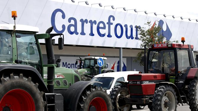 Tractors block the entrance of a Carrefour supermarket during a protest by Belgian dairy farmers against low milk prices in Waterloo