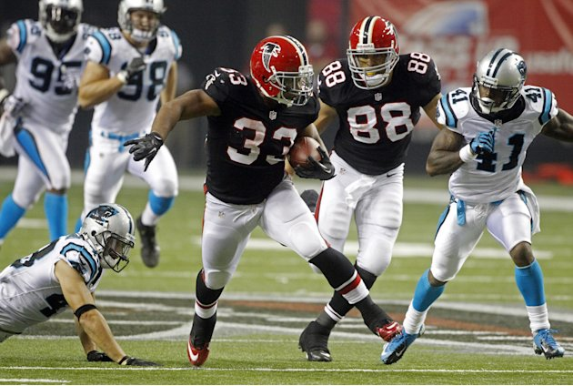 Atlanta Falcons running back Michael Turner (33) runs away from Carolina Panthers cornerback Captain Munnerlyn (41) and  free safety Haruki Nakamura (43) on a second half touchdown run in an NFL footb