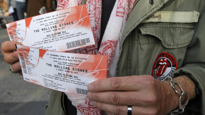 """Rolling Stones fan who named himself as Patrice, 55, and who claims he has seen 54 Rolling Stones concerts, shows the tickets he bought for tonight's concert in Paris, Thursday, Oct. 25, 2012. The Rolling Stones announced a surprise """"warm-up gig"""" in Paris, and within an hour the Champs Elysees was swarming with fans hoping to get satisfaction with one of the 350 tickets for the Thursday night show. (AP Photo/Francois Mori)"""