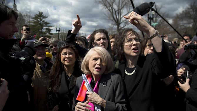 Plaintiff Edith Windsor of New York, center, tries to move through the crowd in front of the Supreme Court in Washington, Wednesday, March 27, 2013. The U.S. Supreme Court, in the second day of gay marriage cases, turned Wednesday to a constitutional challenge to the federal law that prevents legally married gay Americans from collecting federal benefits generally available to straight married couples.  (AP Photo/Carolyn Kaster)