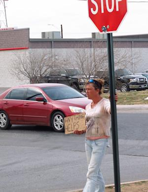 In this photo from Feb. 24, 2014, homeless woman, who gave her name as only Katt, stands on a street corner in Midland, Texas, trying to get donations from motorists. Two Midland police officers were disciplined with a three-day suspension recently for having a contest to see who could confiscate the most signs from homeless people. (AP Photo/Betsy Blaney)