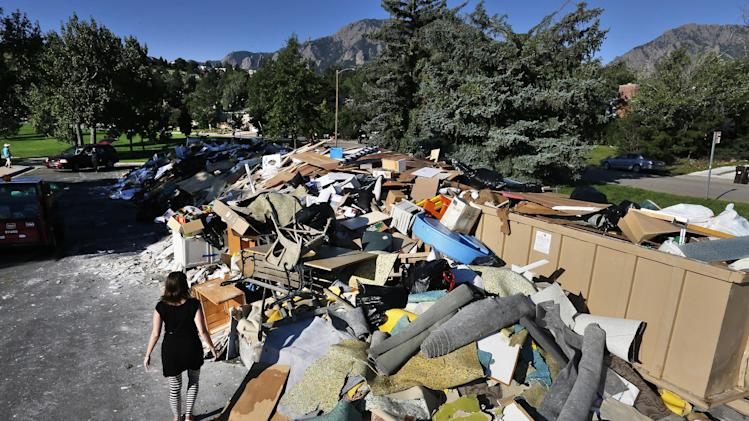 A woman looks for reclaimable wood from a heap of household flooring, furniture and other items destroyed by flooding the previous week, in Boulder, Colo., Friday Sept. 20, 2013. The flood recovery process is underway along the front range of Colorado as people clean out flooded homes and businesses. (AP Photo/Brennan Linsley)