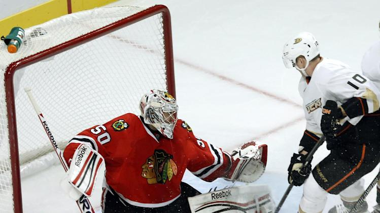 Chicago Blackhawks goalie Corey Crawford (50) makes a save on a rebound attempt by Anaheim Ducks right wing Corey Perry during the second period of an NHL hockey game, Tuesday, Feb. 12, 2013, in Chicago. (AP Photo/Charlie Arbogast)