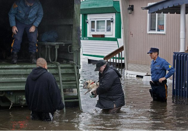 With the aid of New Jersey State police, a man walks with his dog to a National Guard vehicle after leaving his flooded home at the Metropolitan Trailer Park in Moonachie, N.J., Tuesday, Oct. 30, 2012