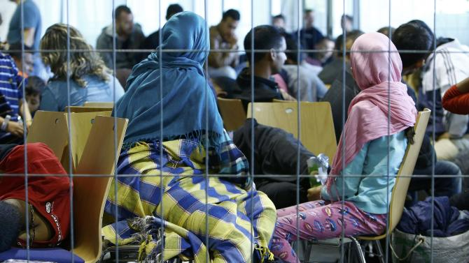 Asylum seekers from various countries rest as they wait to be registered inside a hall, used by German police as the first registration point, in Passau