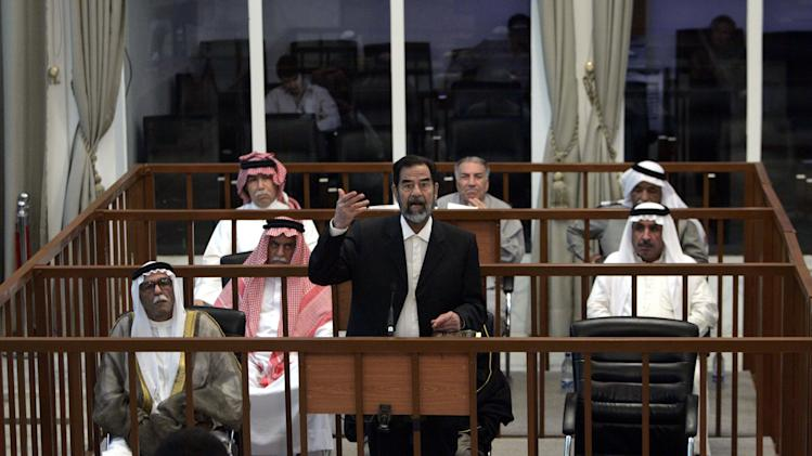 FILE - In this May 17, 2006 file photo, former Iraqi leader Saddam Hussein, standing, testifies at his trial at a court in the heavily fortified Green Zone, in Baghdad, Iraq. The Iraqi government said Wednesday, May 4, 2011, that it will disband a notorious court set up after the 2003 U.S.-led invasion to prosecute Saddam Hussein and other regime members. (AP Photo/Marco Di Lauro, Pool, File)