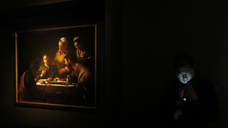 "A security guard checks his mobile phone beside Baroque masterpiece ""Supper at Emmaus"",  (1605-06) by Caravaggio, at a gallery in Hong Kong"