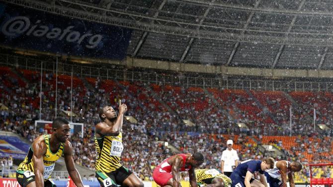 Sunday, Aug. 11, 2013: Jamaica's Usain Bolt gestures skyward as rain falls before the men's 100-meter final at the World Athletics Championships in the Luzhniki stadium in Moscow. (AP Photo/Matt Dunham)