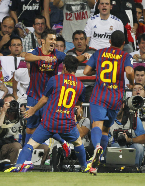 FC Barcelona's David Villa, left, celebrates his goal with Lionel Messi from Argentina, centre, and Adriano Correia from Brazil, right, during a first leg Spanish Supercup soccer match against Real Madrid at the Santiago Bernabeu stadium in Madrid, Spain, Sunday, Aug. 14, 2011. (AP Photo/Andres Kudacki)