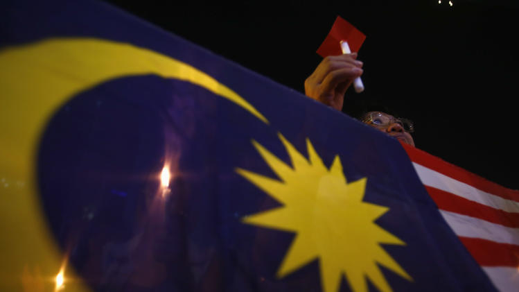 A woman holds a candle near the Malaysian flag during a vigil for victims of downed Malaysia Airlines Flight MH17 airliner, in Subang Jaya outside Kuala Lumpur