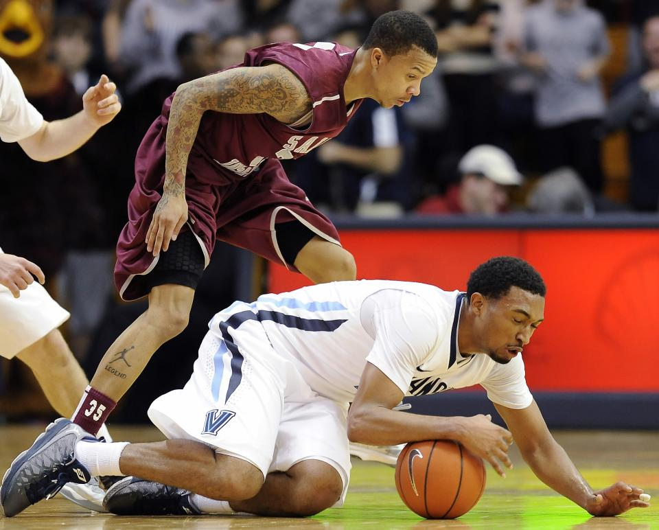Villanova's Darrun Hilliard, right, dives on a loose ball in front of Saint Joseph's Carl Jones during the second of an NCAA college basketball game, Tuesday, Dec. 11, 2012, in Villanova, Pa. Villanova won 65-61. (AP Photo/Michael Perez)