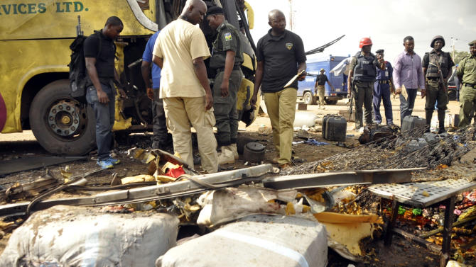 FILE: Police officers inspect a passenger bus following an explosion at a bus station in Kano on July 24, 2014.