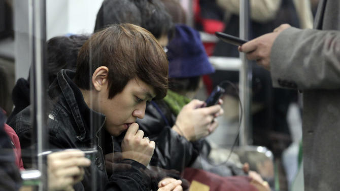 In this Tuesday, Nov. 20, 2012 photo, passengers operate their smartphones on a subway in Seoul, South Korea. Across the entire population, South Korea's government estimated 2.55 million people are addicted to smartphones, using the devices for 8 hours a day or more, in its first survey of smartphone addiction released earlier this year. (AP Photo/Ahn Young-joon)
