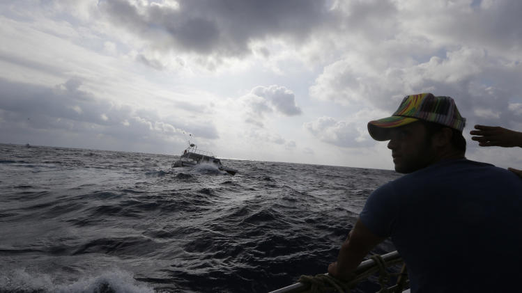 Italian fisherman Cristian Parmisano looks out from a fishing boat at the exact point where the sunken ship which was carrying African migrants towards Italy capsized Thursday, during a commemoration boat flotilla for the victims of the shipwreck, off the Sicilian island of Lampedusa, Italy, Saturday, Oct. 5, 2013. Authorities say the search to recover bodies from the sunken boat has been called off for a second day because of bad weather. The ship capsized after the migrants on board started a fire to attract attention. Just 155 people survived, 111 bodies have been recovered and more than 200 are still missing. (AP Photo/Luca Bruno)