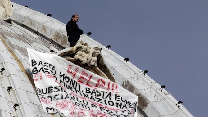"""Italian businessman Marcello di Finizio stands above his banner  which reads in Italian """"Help!! Enough Monti (Italian Premier Mario Monti), enough Europe, enough multinationals, you are killing all of us. Development?? This is a social butchery!!"""", as he protests on St. Peter's 130-meter-high (42-feet-high) dome, at the Vatican, Wednesday, Oct. 3, 2012. An Italian man has eluded Vatican security and scaled the 130-meter-high (42-feet-high) dome of St. Peter's Basilica to protest Italian government and European Union policies. Officials said Wednesday that the man, who identified himself as the owner of a beach resort, refused appeals from government ministers offering to meet with him if he would come down. (AP Photo/Andrew Medichini)"""
