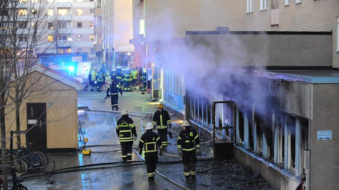 Firemen work outside a still smoking cellar mosque in Eskilstuna, Sweden, Thursday, Dec. 25, 2014. Five of the twenty at prayer inside were taken to hospital after inhaling smoke when a burning object was hurled through a window, setting fire to the building in the early afternoon. (AP Photo/Pontus Stenberg) SWEDEN OUT
