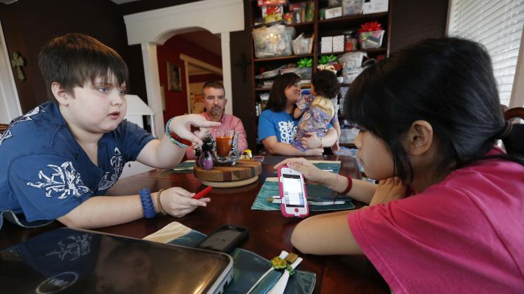 "In this April 4, 2013 photograph, Colton Smith, left, uses a combination of sign language and Google Translate on his iPod to ""speak"" with his new 14-year-old sister, Guan Ya, in the dining room of their Rienzi, Miss., home, as parents  Phillip and Niki Smith listen. The Smiths and their three other children are using the program to communicate almost exclusively with Guan Ya, who is deaf. The family uses iPhones, iPods and a laptop, all loaded with the program to write in either English that translates to Chinese or vice-a-versa. (AP Photo/Rogelio V. Solis)"