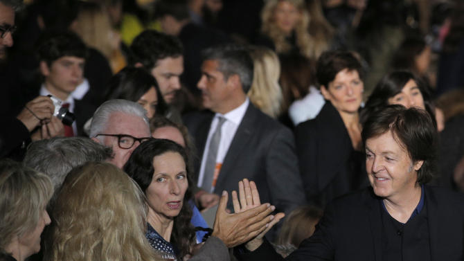Sir Paul McCartney, right, shakes hands after the presentation of his daughter British fashion designer Stella McCartney's ready to wear Spring-Summer 2013 collection, in Paris, Monday, Oct.1, 2012. (AP Photo/Francois Mori)