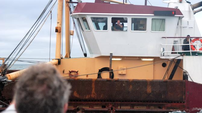 This Oct. 8, 2012 photo shows a  British fisherman at the window of his boat, arguing with a French fisherman, left, as he is prevented from fishing by French fishermen, in the English Channel, off Le Havre, western France. A bumper season for the French national dish of Coquilles St. Jacques has turned into a bitter dispute in the English Channel, as French fishermen angry over British expansion into their waters surrounded British boats in a show of maritime force.(AP Photo/Pierre Guillaume)