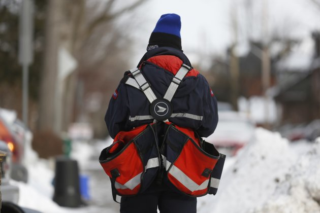 A Canada Post employee delivers mail in Ottawa December 11, 2013. Canada's postal service will phase out urban home delivery within five years and hike the cost of postage stamps to try to stem soaring losses, the post office said on Wednesday. REUTERS/Chris Wattie (CANADA - Tags: BUSINESS EMPLOYMENT)