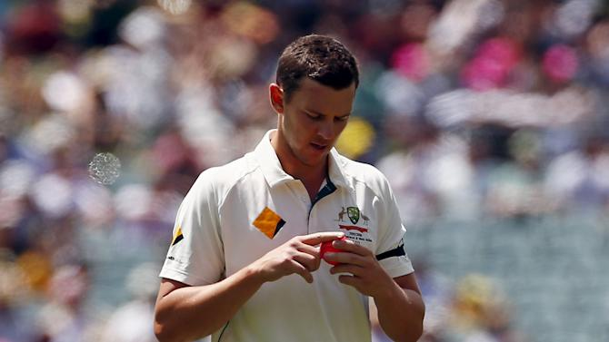 Australia's Josh Hazlewood shines the pink ball as he prepares to bowl during the first day of the third cricket test match against New Zealand at the Adelaide Oval, in South Australia