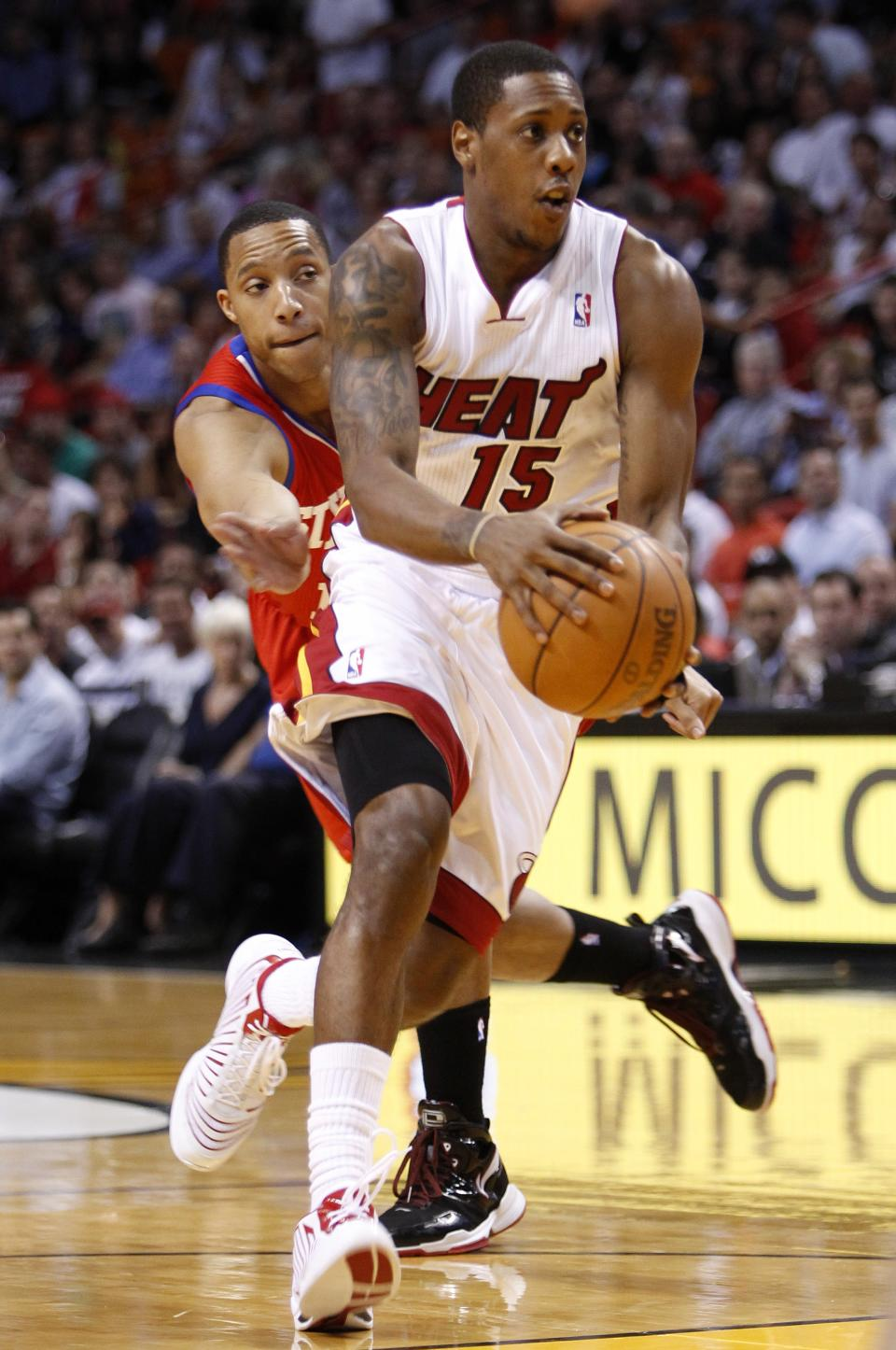 Miami Heat guard Mario Chalmers (15) drives to the basket trailed by Philadelphia 76ers guard Evan Turner during the first half of an NBA basketball game, Tuesday, April 3, 2012 in Miami. (AP Photo/Wilfredo Lee)