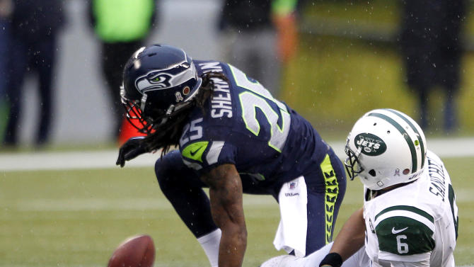 New York Jets quarterback Mark Sanchez, right, looks at his fumble, which was recovered by the Seattle Seahawks, after he was tackled by Seahawks' Richard Sherman, during the second half of an NFL football game, Sunday, Nov. 11, 2012, in Seattle. (AP Photo/Elaine Thompson)