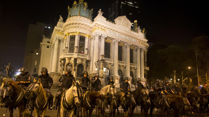Riot police on horses line up in front of the Municipal Theater in Rio de Janeiro, Brazil, Thursday, June 20, 2013. More than half a million Brazilians poured into the streets of at least 80 Brazilian cities Thursday in demonstrations that saw violent clashes and renewed calls for an end to government corruption and demands for better public services. Riot police battled protesters in at least five cities, with some of the most intense clashes happening in Rio de Janeiro, where an estimated 300,000 demonstrators swarmed into the seaside city's central area. (AP Photo/Victor R. Caivano)