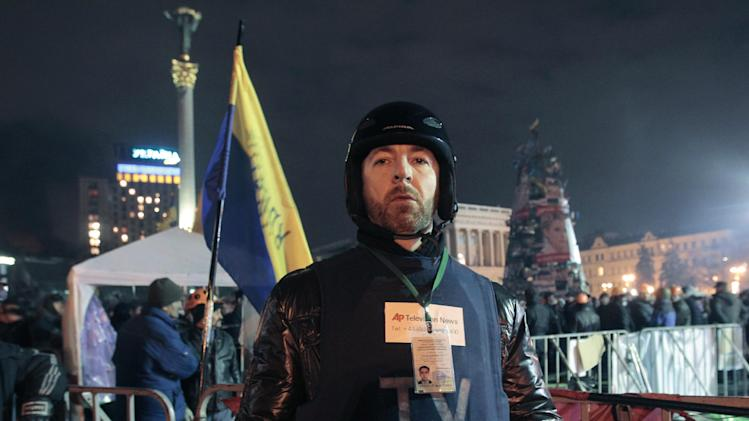 AP reporter Yuras Karmanau poses for a photo in front of a stage on the Independence Square, the epicenter of the country's current unrest in Kiev, Ukraine, Thursday, Feb. 20, 2014. Karmanau reported on Thursday's violence in Kiev that left dozens of people killed and hundreds wounded, the bloodiest day in Ukraine's post-Soviet history.(AP Photo/Sergei Chuzavkov)