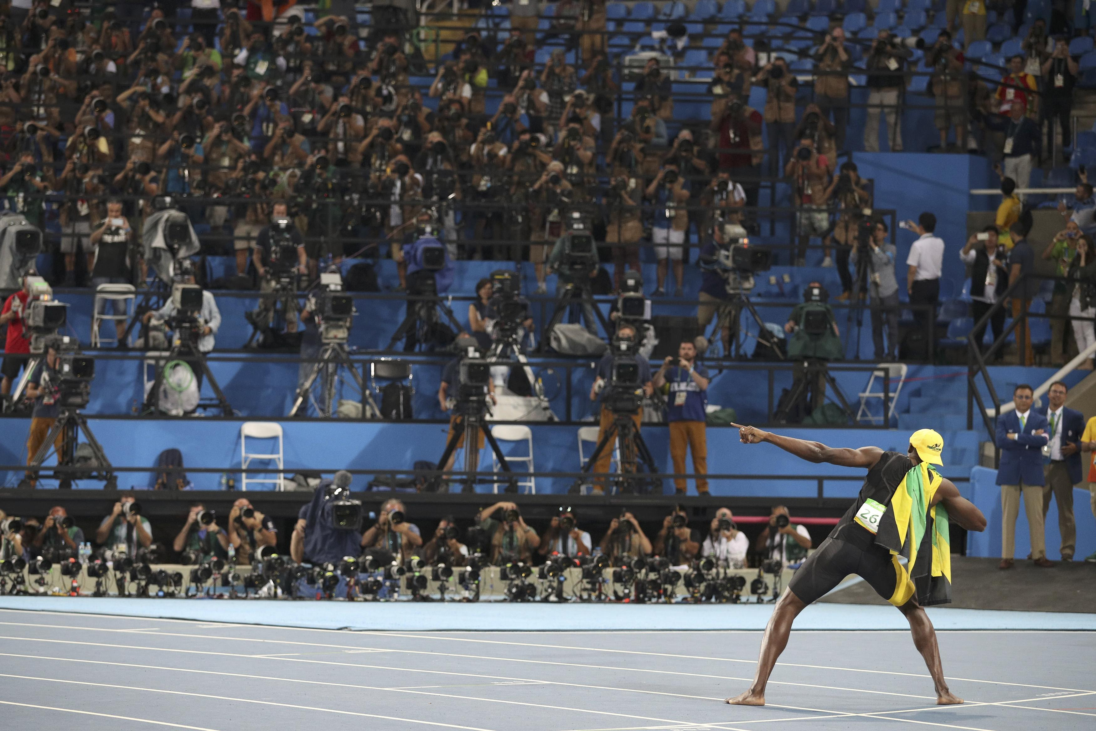 Usain Bolt celebrates his third win in the men's 100M. (REUTERS)
