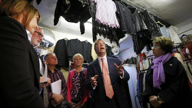 The leader of the United Kingdom Independence Party (UKIP) Farage talks with supporters at a small business that has expressed its support for the party, in Canterbury southern England