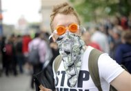 A masked protester with Occupy Wall Street stands on Broadway in New York